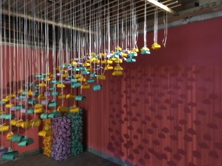 Aerial installation at Room to Breathe with visitors' stories written on folded paper.